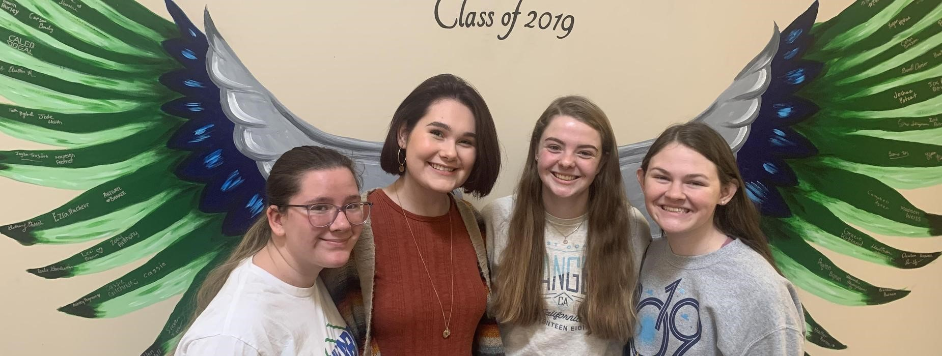 Students in front of wings mural Class of 2019